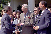 United States President George W. Bush shakes hands with former US Senator Daniel Patrick Moynihan (Democrat of New York) as he participates in a Social Security event in the Rose Garden of the White House in Washington, DC on Wednesday, May 2, 2001.  At far right is Richard Parsons who will chair the commission on Social Security.<br /> Credit: CNP