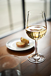 A glass of white wine on a bar with a small plate of bread