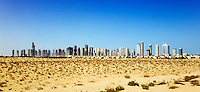 Dubai.  Skyline of the Jumeirah Developments, Emirates Lakes Towers and the Marina Development with new housing developments and desert in the foreground..