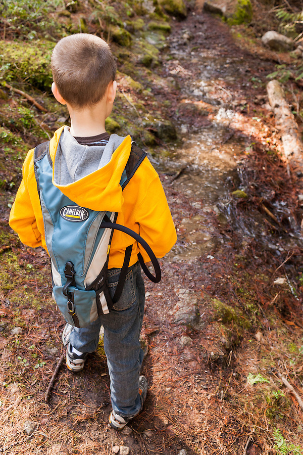 A seven year old boy hikes along a trail in Idaho wearing a bright yellow hoodie and carrying a Camelbak hydration pack.