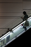 A woman using a smartphone on an escalator in Shinjuku, Tokyo, Japan. Friday April 21st 2017