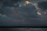 Under a cloud-crowded sky, a red and yellow outrigger canoe makes a pass through the small boat lagoon at San Leandro Marina Park on San Francisco Bay
