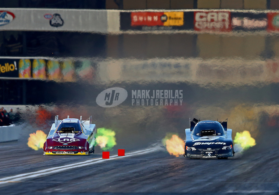 Feb 8, 2014; Pomona, CA, USA; NHRA funny car driver TIm Wilkerson (left) races alongside Cruz Pedregon during qualifying for the Winternationals at Auto Club Raceway at Pomona. Mandatory Credit: Mark J. Rebilas-