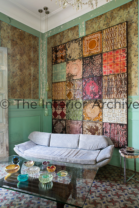 A 1940s wall hanging is displayed behind a retro sofa in the tiled living room