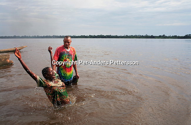 LUKUTU, DEMOCRATIC REPUBLIC OF CONGO MARCH 18: An unidentified women is being baptised by Marcel Makayabu, a pastor in the Congo River on March 18, 2006 in Lukutu port, Congo, DRC. Lukutu, located along the Congo River, is a small village with a palm oil factory and an economy of agriculture and fishing. Congo River is a lifeline for millions of people, who depend on it for transport and trade. During the Mobuto era, big boats run by the state company ONATRA dominated the traffic on the river. These boats had cabins and restaurants etc. All the boats are now private and are mainly barges that transport goods. The crews sell tickets to passengers who travel in very bad conditions, mixing passengers with animals, goods and only about two toilets for five hundred passengers. The conditions on the boats often resemble conditions in a refugee camp. Congo is planning to hold general elections by July 2006, the first democratic elections in forty years..(Photo by Per-Anders Pettersson/Getty Images....