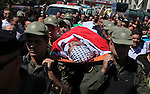 Palestinian security forces carry the body of Raed al-Jabari, 35, during his funeral in the West Bank city of Hebron, September 12, 2014. Al-Jabari died on Tuesday in Israel's Soroka Medical Center after Palestinian officials said he was tortured by Israeli prison guards while being transferred between jails. Photo by Mamoun Wazwaz