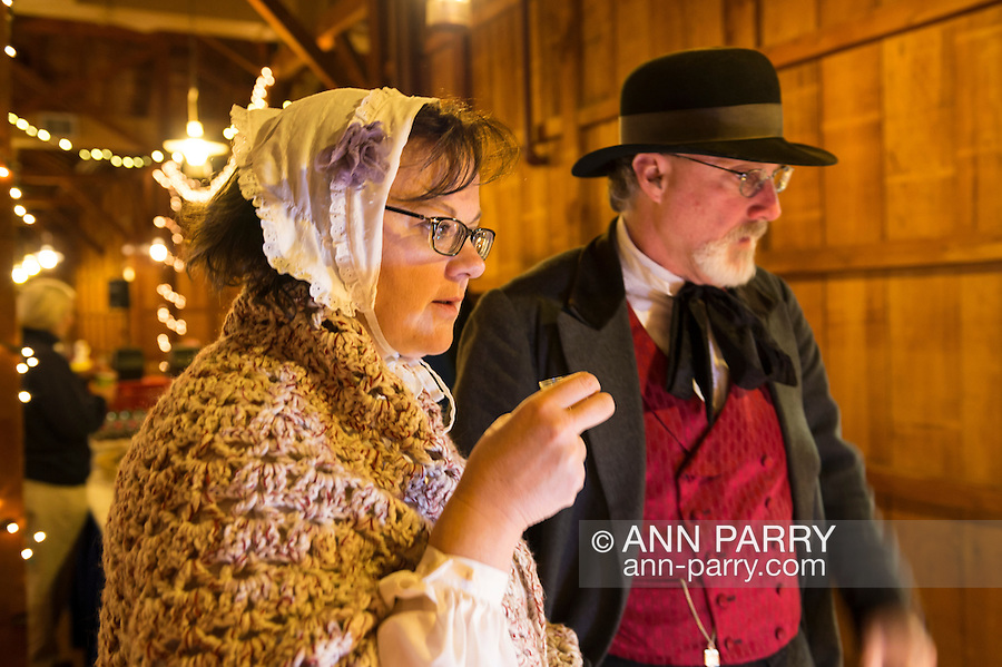 Old Bethpage, New York, USA. December 26, 2014. SHERRI GUTHRIE and husband CHART GUTHRIE, dressed in traditional 19th Century clothing, visit the Salce imported Italian olive oil booth inside the Barn, at night, on the historic, rustic grounds of Old Bethpage Village Restoration, transformed by candlelight and Christmas decorations into a Nineteenth Century holiday experience for Long Island visitors. Candlelight Evenings are held until December 30th.