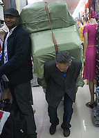 An African man and a Chinese man pulling a cart full of garments are seen in an area of Guangzhou known to locals as 'Chocolate City', Guangzhou, Guangdong Province, China, 08 December 2014. The health authorities of Guangzhou are said to be stepping up their monitoring of the African community in light of the ongoing outbreak of the Ebola virus disease in West Africa.