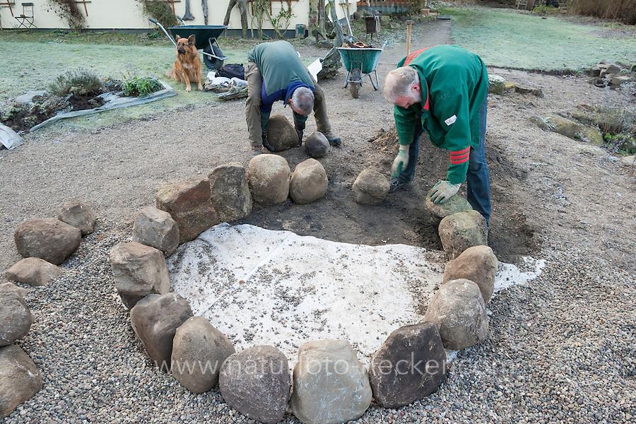 Bau einer Kräuterspirale aus Feldsteinen, Kräuterbeet, Beet, Kräutergarten, Gartenarbeit. Fleece wird am Boden ausgelegt, Verlegen der 1. Steinreihe