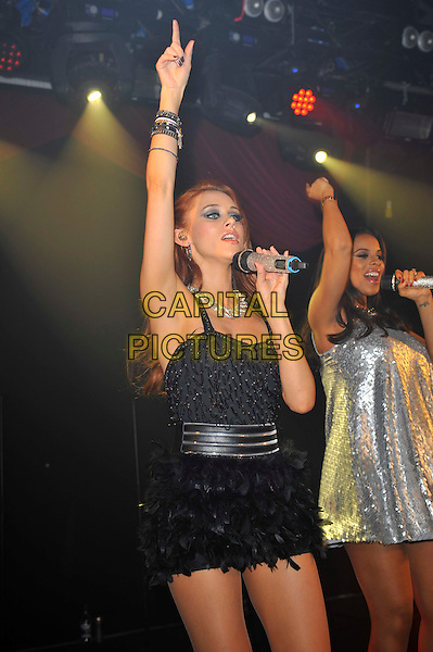 The Saturdays - Una Healy and Rochelle Humes.The Saturdays performing at G-A-Y, Heaven Night Club, London, England, UK, 23rd March 2013..half length music gig live on stage band girl group microphone  dress singing  black  dress feather skirt dancing skirt pregnant singing hand arm raised up .CAP/MAR.© Martin Harris/Capital Pictures.