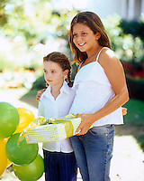 Two girls at a summer birthday party carrying a present