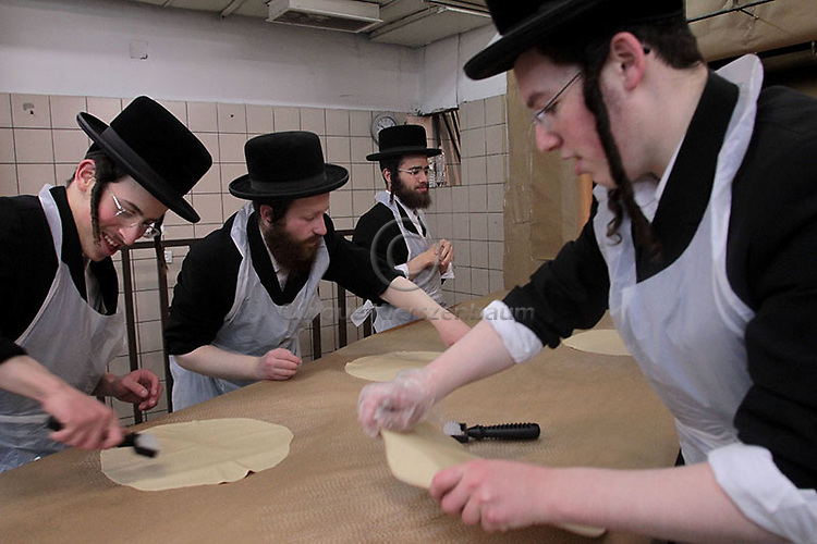 Matzah baking in Belz community in Jerusalem.<br /> <br /> Ultra-Orthodox Jewish men knead the dough before baking the Matzoth or unleavened bread in Jerusalem. Religious and observant Jews throughout the world eat matzoth during the eight-day Pesach holiday (Passover), which begins the April 6, with the sunset to commemorate the Israelis' exodus from Egypt some 3,500 years ago and commemorate their ancestors' plight by refraining from eating leavened food products. Photo: Quique Kierszenbaum.