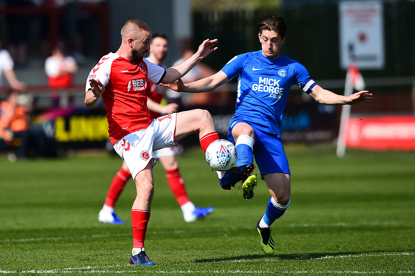 Peterborough United's Alex Woodyard vies for possession with Fleetwood Town's Paddy Madden<br /> <br /> Photographer Richard Martin-Roberts/CameraSport<br /> <br /> The EFL Sky Bet League One - Fleetwood Town v Peterborough United - Friday 19th April 2019 - Highbury Stadium - Fleetwood<br /> <br /> World Copyright © 2019 CameraSport. All rights reserved. 43 Linden Ave. Countesthorpe. Leicester. England. LE8 5PG - Tel: +44 (0) 116 277 4147 - admin@camerasport.com - www.camerasport.com