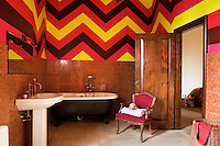 Artist Andrea Burroni devised a daring geometric pattern in bright colours to complement the pink Verona marble wall tiles in this bathroom