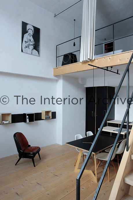 """In this space the bedroom is situated on a mezzanine reached by a cast-iron staircase; underneath the dining table is surrounded by Charles Eames """"Plastic Side Chairs"""" and the modular shelving is made of plywood and steel; the photograph is by Hemut Newton"""