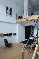"In this space the bedroom is situated on a mezzanine reached by a cast-iron staircase; underneath the dining table is surrounded by Charles Eames ""Plastic Side Chairs"" and the modular shelving is made of plywood and steel; the photograph is by Hemut Newton"