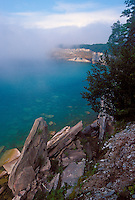 The cliffs of Pictured Rocks National Lakeshore in the fog and the rock formation called Sail Rock, bottom, near Munising, Mich.