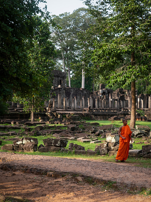 A lone Buddhist Monk reflecting in a pool of water at the Bayon Temple during the Monsoon Season, Angkor Wat complex, Cambodia