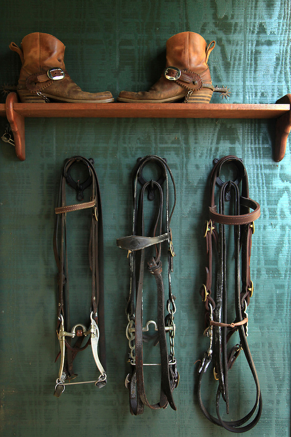 "Cowboy boots and tack are on display outside veterinarian Dr Billy Bergin's Paniolo Preservation Society offices in Waimea, Hawaii.  Dr. Bergin has long treated the Hawaiian cowboys' horses and cattle and founded the Paniolo Preservation Society to promote the preservation of paniolo history and culture.  He has a large collection of historical photographs and items related to the history of cowboy culture in Hawaii. ""There have been cowboys in Hawaii longer than in the west and their history is worth preserving,"" says Bergin of his reason for founding the preservation society."