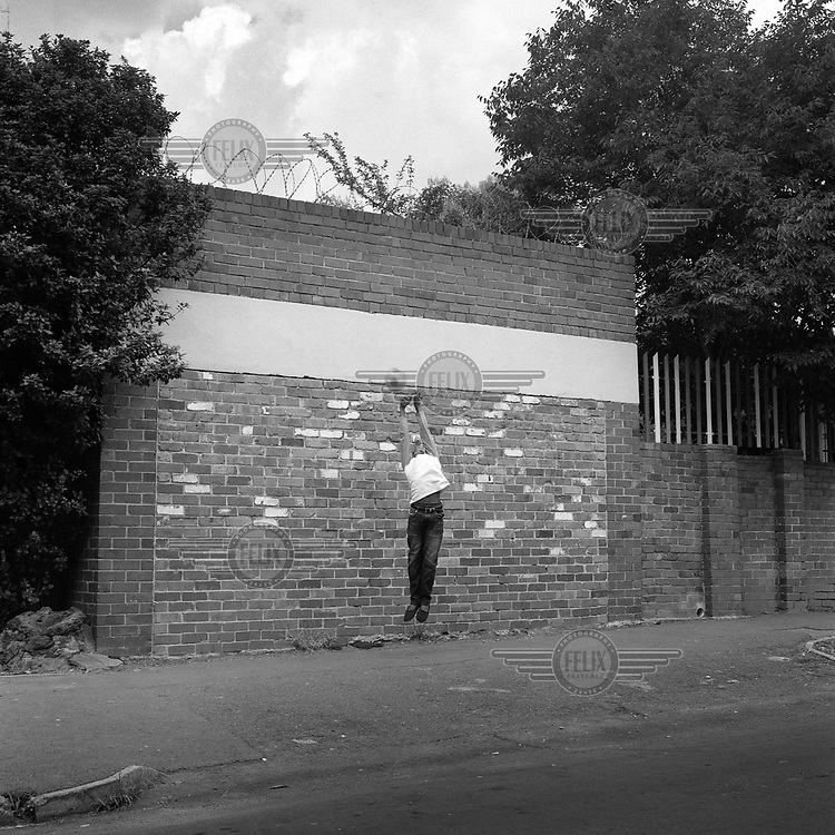 A goalkeeper tries to make a save during a street football match on Kenmere Road, Yeoville.