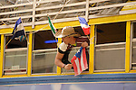 The Hispanic Parade in New York City. A boy hangs out the window of a bus decorated with flags from Latin American countries in the Hispanic Parade in New York City.