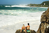 USA, Hawaii, Oahu, the North Shore, young women relax on the rocks and watching the surfing at Waimea Bay