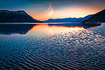 Sunset at Turnagain Arm of Cook Inlet. A rippled tidal flat revealed during low tide. Chugach Mountains in the background. Southcentral Alaska, Summer.