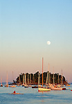 Boats near Curtis Island as the moon rises in Camden, Maine, USA