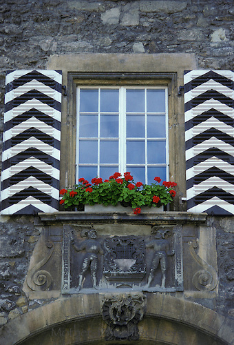 Window in Germany with unique shutters and highlighted with windowbox of red geranuims