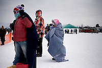 Spectators watch the Whitefish Skijoring World Championship event in Whitefish, Montana, USA.  Skijoring is a competitive sport in which a person on skis navigates an obstacle course while being pulled behind a galloping horse.