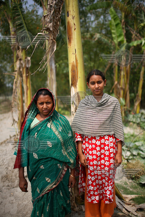 17 year old Rasheda Khatun stands with her mother in the grounds around her home in the Dawabari river bed area. 'Chars' such as this - islands that are periodically submerged by the country's mighty rivers - are home to over five million people in Bangladesh. Life for the char dwellers is hazardous and uncertain. Flooding is common, as is loss of land and erosion, making it a struggle to grow enough food, and meaning families often need to relocate.