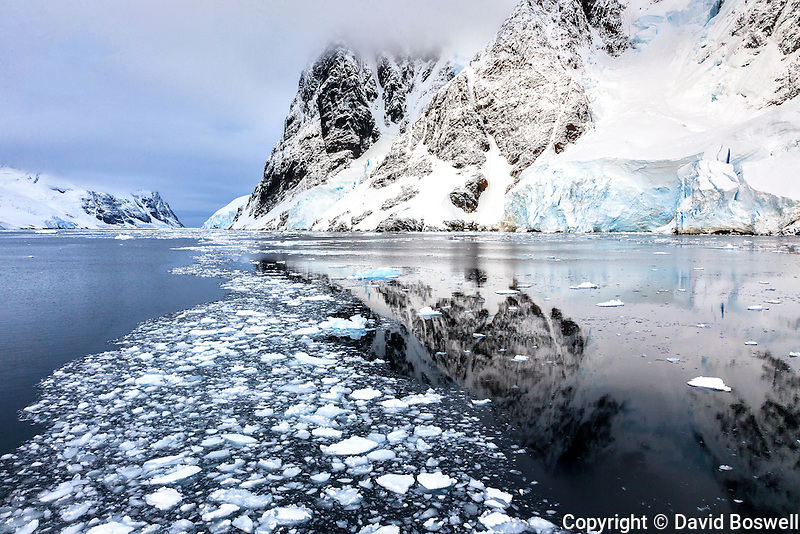 Brash ice and reflections add to the atmosphere of passage through the Lemaire Channel, along the coast of the Antarctic Peninsula.