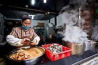 Una donna durante la preparazione di cibo in un ristorante di Wuzhen.<br /> Wuzhen &egrave; una piccola citt&agrave; della provincia dello Zhejiang chiamata anche la Venezia d'Oriente per la caratteristica dei canali che corrono lungo i vicoli dell'antica citt&agrave;. E' anche riconosciuta come uno dei centri pi&ugrave; importanti per la produzione e la lavorazione della seta nell'antichit&agrave;. Ancora sono presenti alcune piccole ditte che continuano a lavorare la seta con gli stessi metodi di come si faceva da secoli. Nonostante sia diventata una meta turistica ancora si pu&ograve; respirare la vecchia Cina passeggiando tra i vecchi vicoli costruiti con la pietra e rimasti intatti nei secoli.