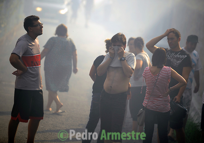 A group of people are seen around the fire area in Os Anxeles, in Brion, on August 16, 2010, near A Coruna.  Pedro ARMESTRE