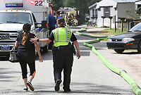 NWA Democrat-Gazette/DAVID GOTTSCHALK  Corporal Kristin Mercado (right), with the city of Fayetteville Police Department, escorts a neighbor Monday, June 12, 2017, to check on her property at Country Lane Mobile Home Park in Fayetteville following a fire at a manufactured home near her home. City of Fayetteville emergency response personnel responded to a structure fire at 10:10 A.M. at 201 East Applelby. The fire is under investigation. No injuries were reported at the scene.