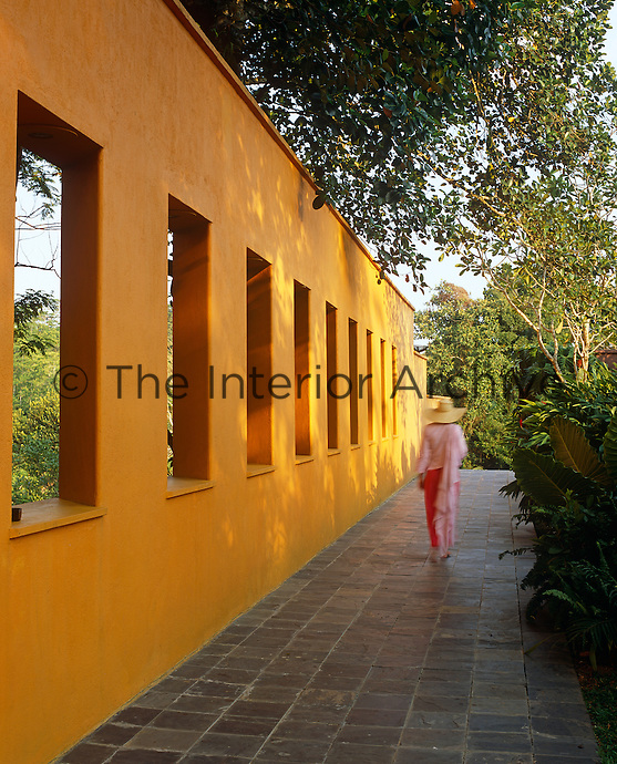 A traditional stone path runs alongside the spectacular saffron-yellow wall which divides the guest area of the villa from the main living space