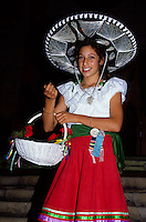 Young and pritty mexican girl in traditional costume carrying a big hat and a flower basket