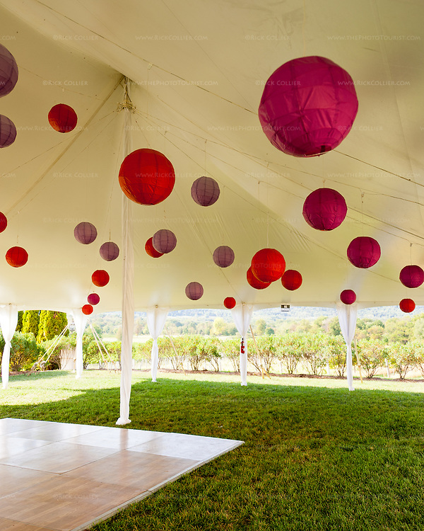 Decorative Chinese lantern balls hang from the ceiling, above a dance floor installed in the events tent in the side yard at Breaux Vineyards.