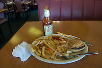 Leftover hamburger and french fry meal with dirty, well worn ketchup catsup bottle in restaurant diner.
