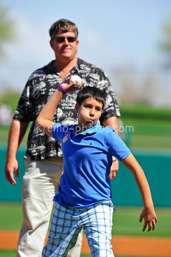 Mar 7, 2011; Tucson, AZ, USA; Dallas Green (blue shirt) throws out a ceremonial first pitch as father John Green looks on prior to a charity exhibition game at the Kino Sports Complex to benefit the Christina-Taylor Green foundation.  John is the father and Dallas the brother of Christina-Taylor who was the 9-year-old girl that was shot and killed during the January assassination attempt on Rep.  Gabrielle Giffords.