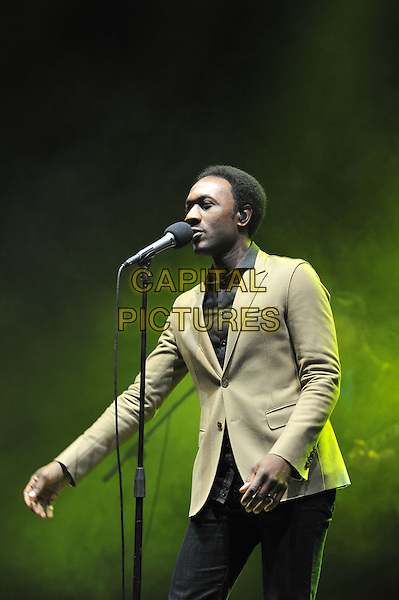 Aloe Blacc.performing live in concert, Hammersmith Apollo, London, England, UK,.15th December 2011..music concert gig live on stage half length microphone singing black shirt  beige jacket blazer .CAP/MAR.© Martin Harris/Capital Pictures.
