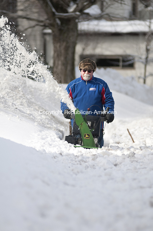Torrington, CT - 14 Feb. 2014 - 021414AJ03 - Jim Reilly, of Torrington, clears snow along his Elm Street sidewalk with his John Deere snowblower Friday afternoon. Reilly had about 18 inches of heavy, wet snow to remove between his house and the corner of Brightwood Avenue where he keeps the sidewalk clear in front of an abandoned house. Alec Johnson/ Republican American