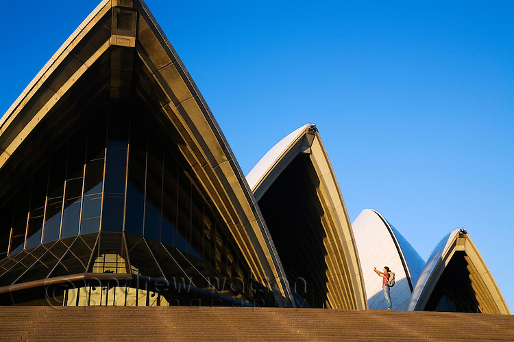 A backpacker photographs the iconic roofs of the Opera House at sunset.  Sydney, New South Wales, AUSTRALIA.
