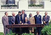 Minister of Foreign Affairs of Israel Shimon Peres puts his signature on the agreement during the signing ceremony of the historic Israeli-PLO Agreement, known as the Oslo 1 Accord, on the South Lawn of the White House in Washington, DC on September 13, 1993.  Pictured, from left to right: From left to right are: Foreign Minister Andrei Kozyrev of Russia; Prime Minister Yitzhak Rabin of Israel; unknown aide; United States President Bill Clinton; Peres; Chairman Yasser Arafat of the Palestine Liberation Organization (PLO); US Secretary of State Warren Christopher; and Arafat aide Mahmoud Abbas.<br /> Credit: Arnie Sachs / CNP