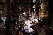 A family sits together to watch television in their house in A Si Gyi village in Pyapon district of Myanmar.