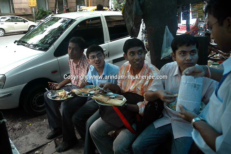 Young office workers having meal during break at  a street food stall in Dalhousie area of Kolkata. Street food stalls are serving the office goers for decades. All kind of Indian foods are available on the street at an affordable price. They sale them openly. Street food stalls are another results of unempoloyment and over poppulation. They serve millions of people in India. Kolkata, West Bengal,  India  7/18/2007.  Arindam Mukherjee/Landov
