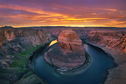 Epic sunset light gives a warm glow to the canyon walls around lake Powell at Horseshow Bend.
