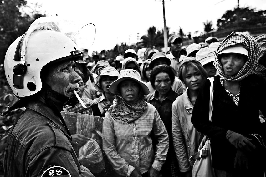 A policeman smokes a cigarette while villagers from Omlaing Commune in Kampong Speu province's Thpong district protest the arrest of village representatives You Tho and Khem Vouthy outside the Kampong Speu Provincial Court, March 24, 2010. The two were arrested for their alleged involvement in the torching of a makeshift office belonging to the Phnom Penh Sugar Company, which is owned by CCP Senator Ly Yong Phat. The company has been granted a 9,000-hectare land concession in Omlaing commune, which rights groups say could be in violation of Cambodia's Land Law if, as suspected, owner Ly Yong Phat is also the beneficiary of an adjacent 10,000-hectare land concession. Under the Land Law, concessions are limited to 10,000 hectares.