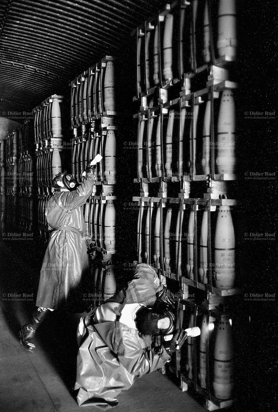 """Usa. Utah. Tooele county. Deseret chemical depot. Two workers, wearing gas masks,boots, protective suits and flashlights, follow the firt entry procedures and look for any leakages in a earth covered igloo which provides secure storage for the weapons. 155 mm GB Nerve Agent, called also """" Sarin"""". Tooele chemical agent disposal facility (TOCDF). Program for destruction of chemical weapons and agent. Incinerating plant. Deseret chemical depot is distant 100 km from Salt Lake City. The Deseret Chemical Depot is one of eight Army installations in the U.S. that currently store chemical weapons. The weapons originally stored at the depot consisted of various munitions and ton containers, containing GB and VX nerve agents or H, HD, and HT blister agent. The Tooele Chemical Agent Disposal Facility is designed for the sole purpose of destroying the chemical weapons stockpile located at the depot. © 1998 Didier Ruef"""