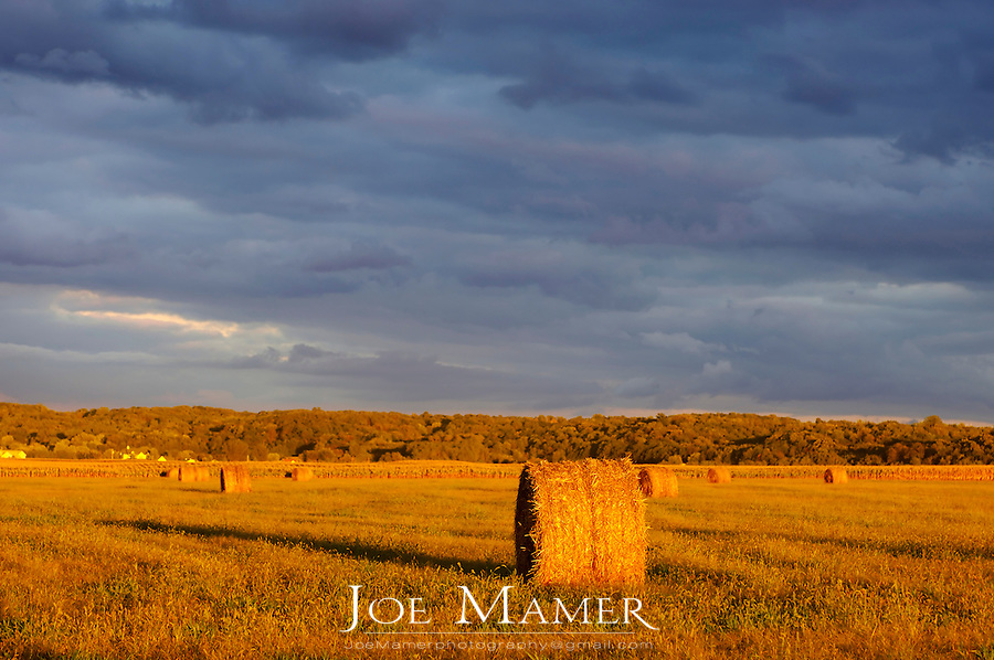 Straw bale in field with overcast gray sky.
